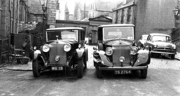 WG 18 - 1933 ROLLS ROYCE LIMOUSINE OWNED BY TOMMY HUNTER SON OF THE FAMOUS ALEX 'COCKY' HUNTER, SECOND-HAND DEALER, OUTSIDE THEIR PREMISES - THE OLD SICK CHILDRENS HOSPITAL, CASTLEHILL TERRACE, ABERDEEN, WITH YS 2764, A 1935 ROLLS ROYCE LIMOUSINE